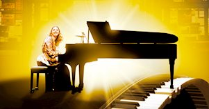 Carole King toca un piano durante el musical Beautiful, de Broadway, frente a un escenario amarillo.