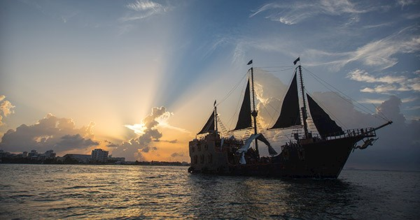 Barco pirata Jolly Roger navegando no mar de Cancún ao pôr do sol.