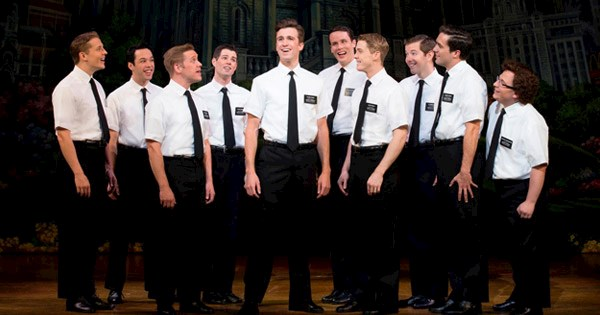 Atores do musical The Book of Mormon em cena no palco.