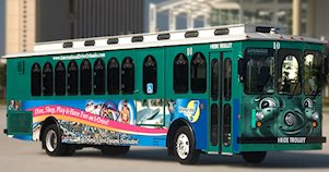 Um bonde verde do I-Ride Trolley, em Orlando, na International Drive