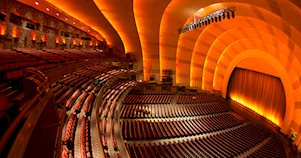 A vista de dentro do teatro Radio City Music Hall em Nova York. Pode-se ver as poltronas e o cenário.