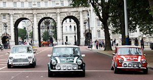 Se ven de frente 3 mini coopers que transitan por una calle de Londres